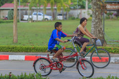 Grandmother and grandson riding bicycle in park Stock Images