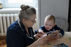 Grandmother and grandson. The grandmother with the grandson sit at a table and consider photos Stock Photos