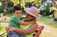 Grandmother and grandson are sitting in the summer garden stock image
