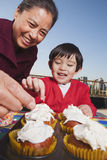 Grandmother and grandson smiling and decorating cupcakes Stock Photography