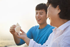 Grandmother and Grandson Smiling and Looking At Seashell Stock Image