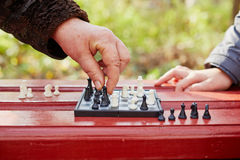 Grandmother hand makes move on chessboard in game in park Stock Images