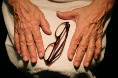 The grandmother hands and glasses for vision. Stock Photo