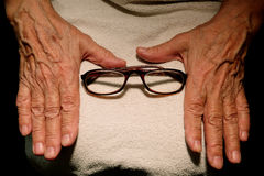 The grandmother hands and glasses for vision. Royalty Free Stock Photography