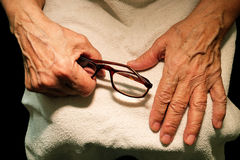 The grandmother hands and glasses for vision. Royalty Free Stock Photo