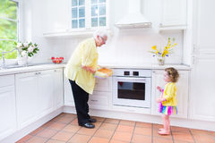 Grandmother and happy girl baking pie in white kitchen Stock Photos
