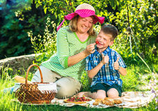Grandmother having a picnic with grandchild. In the garden stock photography