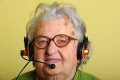 Grandmother with headphones Stock Image