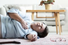 Grandmother with heart attack lying on the floor alone. At home stock image