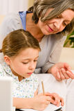 Grandmother help granddaughter doing homework Stock Photo