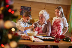 Grandmother helping grandchildren preparing Christmas cookies. Holiday season royalty free stock image