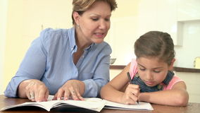 Grandmother Helping Granddaughter With Homework. Grandmother and granddaughter sitting at table together doing homework.Shot on Sony FS700 at frame rate of 25fps stock footage