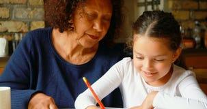 Grandmother helping granddaughter in studies in kitchen 4k stock video
