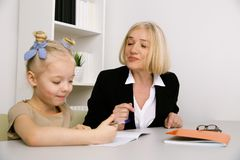 Grandmother helping granddaughter and talking to her. stock image
