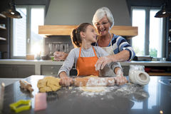 Grandmother helping granddaughter to flatten dough Royalty Free Stock Images