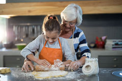 Grandmother helping granddaughter to flatten dough Royalty Free Stock Image