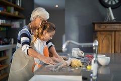 Grandmother helping granddaughter to flatten dough Stock Images