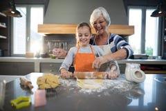 Grandmother helping granddaughter to flatten dough Stock Photography