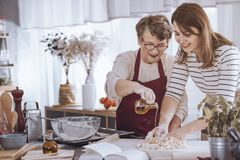 Grandmother adding oil to dough. Grandmother helping her granddaughter make dough by adding olive oil royalty free stock photo