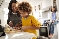 Grandmother helping her granddaughter prepare food in the kitchen, mother sitting in the background, focus on foreground royalty free stock image