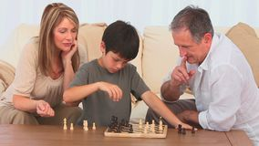 Grandmother helping her grandson to play chess Royalty Free Stock Photography
