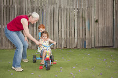 Grandmother helping kids ride trike Stock Photo