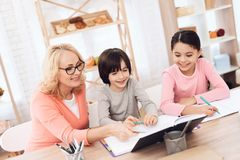 Grandmother helps to make lessons for grandchildren. Beautiful granny helps children learn. Education at home. Heavy homework at school. Decisions of school Royalty Free Stock Images