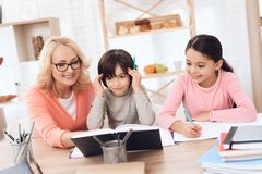 Grandmother helps to make lessons for grandchildren. Beautiful granny helps children learn. Education at home. Heavy homework at school. Decisions of school Stock Images