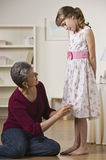 Grandmother Hemming Granddaughter's Dress Stock Photo