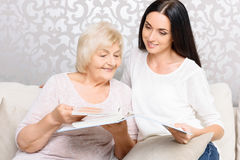 Grandmother with her daughter holding book Royalty Free Stock Photos