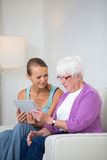 Grandmother with her grand-daughter sitting on a sofa Stock Photo
