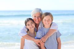 Grandmother with her grandchildren. Enjoying on the beach Royalty Free Stock Photo