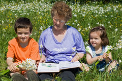 Grandmother with her grandchildren. Grandmother reading to her happy grandchildren a tale royalty free stock photo