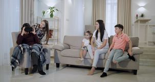 Grandmother with her grandchildren and a mature mother spending a time together on the sofa exploring a new virtual stock video