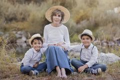 Grandmother with her grandchildren. Sitting in the field Royalty Free Stock Photo