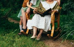 Grandmother with her grandchildren sitting in a rocking chair in the garden and watching an old album with photos, recounts and re royalty free stock photography