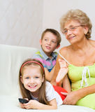 Grandmother with her grandchildren are watching TV. While sitting on a couch stock photography