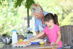 Grandmother and her granddaughter makin an apple pie Stock Photo
