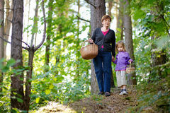 Grandmother and her granddaughter picking berries. In the forest Stock Photography