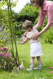 Grandmother with her granddaughter watering flowers in the garde Stock Image