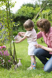 Grandmother with her granddaughter watering flowers in the garde Royalty Free Stock Photography