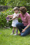 Grandmother with her granddaughter watering the garden Stock Images