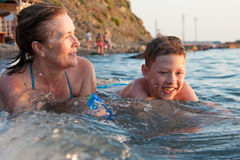Grandmother with her grandson bathing in the sea Stock Image