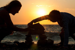 Grandmother with her grandson on the beach at sunset. Grandmother with her grandson on the beach building a castle from a pebble Stock Image