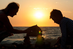Grandmother with her grandson on the beach at sunset. Grandmother with her grandson on the beach building a castle from a pebble Royalty Free Stock Photography