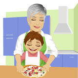 Grandmother with her grandson preparing delicious pizza together in kitchen Royalty Free Stock Photos
