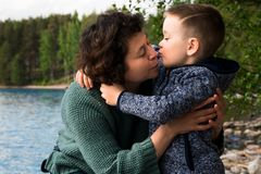 Grandmother and her grandson sitting and hugging hear the sea. Happy kissing family. Royalty Free Stock Photos