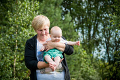 Grandmother and little grandson. Grandmother and her little boy half a year infant baby grandson in outdoors park Royalty Free Stock Images