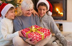 Grandmother With Her Two Grandchildren, Holding A Christmas Gift. Grandmother Sitting With Her Two Grandchildren, Holding A Christmas Gift Royalty Free Stock Photography