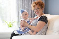 Grandmother hold little baby girl cute smiling close-up in sofa Royalty Free Stock Photos